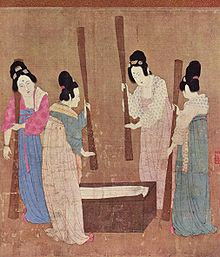 A painted image of four Chinese women wearing colorful silk robes, their hair tied up into buns, standing around a small wooden block with silk laid on top while holding large whisks which they use to beat the silk.