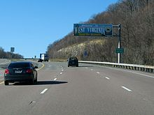 "A sign above the highway reads ""Welcome to West Virginia - Open For Business."" An adjacent sign reads ""Preston County."""
