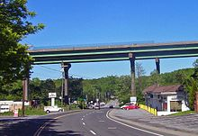 A pair of bridges pass from left to right on tall supports that tower over the other structures in the area, such as telephone poles and single-story buildings. The two-lane NY 22 passes underneath the bridge and proceeds into the background.