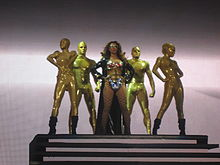 A brunette woman is standing in front of some stairs. She wears a super heroine costume, compound of a golden bra with red diamonds, silver pants, a long black coat and glasses. Behind her five people, dressed like golden mannequins, are standing in different positions.