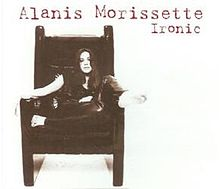 "A barefoot white-skined woman is sitting on a big chair with armrests. She rests her right foot on the left armrest, while she crosses her left leg in front of her body. The background is white, and the words ""Alanis"", ""Morissette"" and ""Ironic"" are written in red letters at the upper right corner."