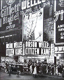 "Night time view of a busy city street. Crowds gather on the sidewalk outside a cinema. A black limousine is parked outside the cinema. The entrance to the cinema has a pair of neon signs which reads ""Orson Welles Citizen Kane"". The rest of building is covered in neon advertising signs."