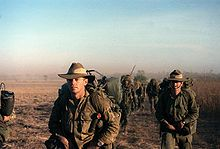 A group of men wearing green military uniforms walking across barren ground.