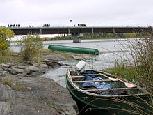 Two canoes sit on the rocky bank of a river in front of a large concrete bridge with vehicles driving across it