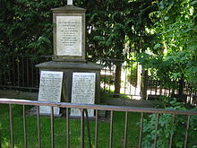 A picture of a grave, with trees, bushes, and a fence in the background and foreground. The grave itself has three markers, with carved text on it.