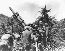 A group of soldiers readying a large gun in some brush.