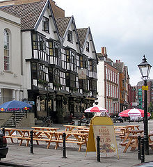 A seventeenth century timber framed building with three gables and a traditional inn sign showing a picture of a sailing barge. Some drinkers sit at benches outside on a cobbled street. Other old buildings are further down the street and in the background part of a modern office building can be seen.