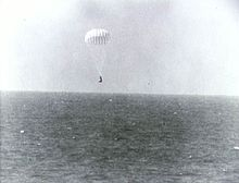 A conical black spacecraft falling towards the surface of the ocean under a single white parachute, seen from some distance away. Very little detail can be seen.