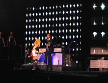 A faraway image of a blond woman, wearing a red shorts, black T-shirt and playing a white electric guitar. Her face is away from the image. Beside her, a band stands with the backdrops displaying white stars on black.