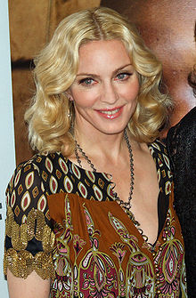 Upper body of a middle-aged blonde woman. Her hair is parted in the middle and falls in waves to her shoulder. She is wearing a loose dress with black and brown prints on it. A locket is hung around her neck, coming up to her breasts. She is looking to the right and is smiling.