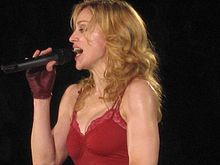 A female blond performer wearing a red top. She is holding a microphone in her brown-gloved right hand.