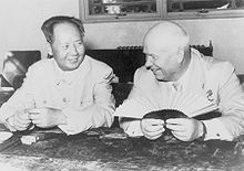 A balding man and a younger Chinese man sit and smile, the balding man holding a fan