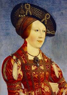 Woman in a heavily embroidered red dress wears an ornate hat with pearls and netting
