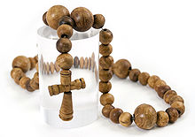 A necklace made out of slightly irregular wooden beads with a small, carved wooden cross in the middle, displayed on top of a transparent plastic cylinder against a white background