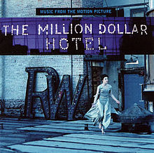 "A blue-tinted photograph of a Caucasian woman in her 30's—Milla Jovovich—running barefoot across the rooftop of a brick building wearing a long dress. Above her are the captions ""MUSIC FROM THE MOTION PICTURE"" written in blue on black and ""THE MILLION DOLLAR / HOTEL"" written with light bulbs."