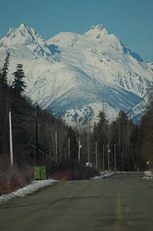 A glaciated mountain rising above trees and a paved road.
