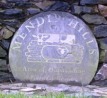 Weathered blue circular plaque bearing the logo of the Mendip Hills Area of Outstanding Natural Beauty
