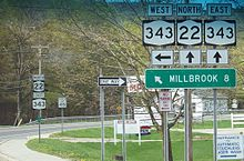 A sign assembly indicates that NY 343 westbound is accessed by turning left while NY 22 northbound and NY 343 eastbound are straight ahead. A sign below the route shields indicates that Millbrook is located eight miles to the west on NY 343.