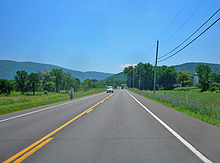 A two-lane highway in a grassy area with a telephone line on the right and mountains in the distance.