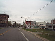 A two-lane highway approaches an intersection with another highway regulated by a blinking signal. Small, mostly two-story buildings surround the rural junction. A sign assembly indicates that NY 22 northbound and US 11 southbound turn left while US 11 northbound is straight ahead.
