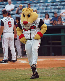 "A person wearing a yellow anthropomorphized cougar costume, in which only the head and arms are visible, and dressed in a white baseball uniform with ""Sounds"" written across the chest in red letters dances on a baseball field"
