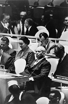 An older man sits among United Nations delegation tables, looking at the camera.