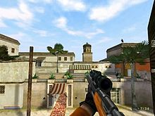 Screenshot from a first-person perspective, showing the player's character on a mission, looking out from a window, at a hotel across the street in Morocco. An assassin can be seen on a rooftop, getting ready to assassinate a person.
