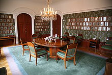 A room with pictures on the walls. In the middle of the room there is a wooden table with chairs around it.
