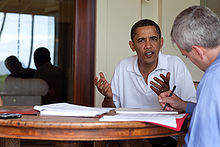 Obama, wearing a white shirt, is moving his hands while talking to a man in a blue shirt, who sits across him.