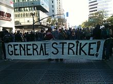 "The front of a marching crowd carrying a large banner. The banner reads ""General Strike!"""