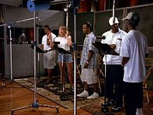 A woman and four men recording a song in a studio.