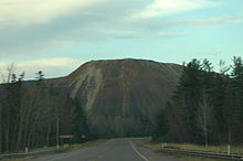 A roadway leading away into the distance before curving in front of a large pile of waste rock