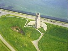Arial photograph of a white stone tower near the shore