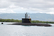 A submarine travelling on the water's surface near to shore, with trees and mountains in the background.