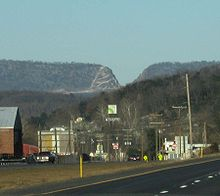 A small town is seen below a mountain ridge which contains a deep V-shaped cut.
