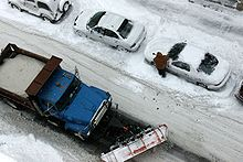 Street seen from above covered in snow with a city truck full of snow and a person who has to remove snow from his or her car