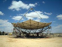 A horizontal parabolic dish, with a triangular structure on its top. Around it is a flat sandy area, with desert in the background. It's a sunny day, with a few white clouds in the blue skies.