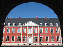 Through the archway of a gate is visible a wide part of the red-brick façade of a two-storey building, with large windows outlines with white stone arches. They grey roof shows skylight windows of a third floor. The entrace is preceded by a small set of steps and is surmounted by an ornament showing two figures supporting a coat of arms.