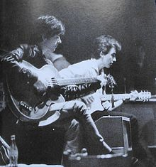 Black-and-white picture of two young men playing electric guitars, the guitarist in the foreground wearing a leather jacket and the one in the background a white collared shirt. Other individuals are visible in the background
