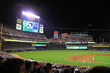 "Baseball field at night, scoreboard displays a player, Twins ""M"" and ""Stp"" decorate a large neon sign"