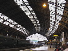 A railway station with curved platforms under an arched iron framed roof with roof-lights. A passenger train stands at the platform on the right and on the left passengers waiting for a train.