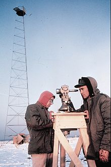 Picture of a man taking measurements with a theobolite in a frozen environment.