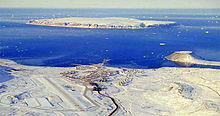 Aerial photograph of Thule Air Base with North Star Bay in the background. Land masses are show covered in snow, but the bay is not frozen over.