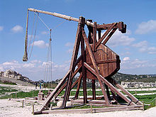 A tall wooden structure with a throwing arm counter-balanced by a large weight