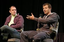 Two adult males sitting in chairs; the male at the right is speaking into a handheld microphone