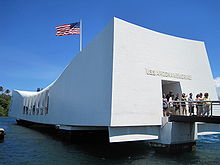 white rectangular memorial building with U.S. flag flying above