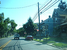 A two-lane road in a residential area with signs on the right side of the road reading north Route 45 left and east U.S. Route 40 straight