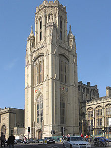 A tall stone nineteenth century with shields on the visible sides and a pepperpot upper storey. In front, traffic and pedestrians on a busy street.