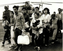 Twelve refugees of varying ages, carrying bundles of possessions, arrive on the deck of a United States naval vessel. Three US airmen, as well as a helicopter, are visible in the background.