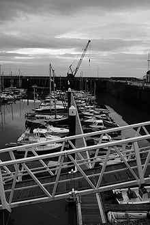 small boats lined up in harbour. Crane in the background & metal walkway in the foreground.